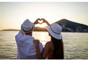 在海边比爱心手势的恩爱夫妻