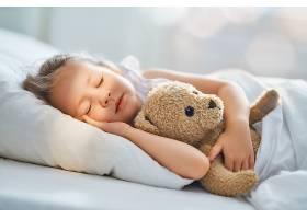 拿玩具睡觉的小女孩