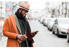 街拍休闲橙色外套穿针织衫的黑人男子