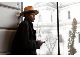 在室内观望窗外的黑人男子