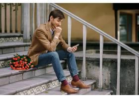 坐在楼梯上等人的时尚休闲男子