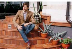 坐在楼梯上的时尚休闲男子