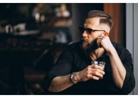 坐在咖啡厅一边喝酒等人的男子