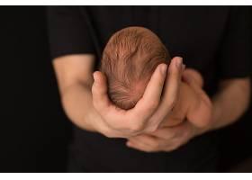 手里抱着刚刚出生的婴儿的人