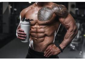 拿着饮水杯的肌肉教练肌肉展示
