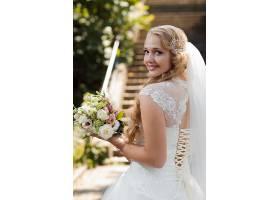 拿着花卉的年轻漂亮婚纱新娘