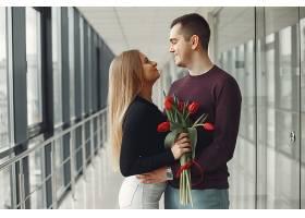 一对欧洲夫妇手持一束红色郁金香站在大厅里_728237501