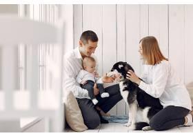 美丽的一家人在卧室里和一只狗共度时光_739746601