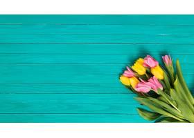 黄色绿色木桌上方有粉色郁金香花朵的俯视_408569701