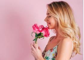 粉色背景下手持玫瑰花的金发年轻女子微笑的_386573801图片