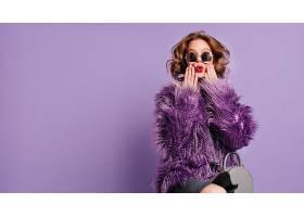 一位化妆时髦的年轻女子在鲜艳的紫色背景上_1097962201