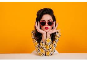 美女戴着心形眼镜摆姿势坐在黄色背景上的_1243061101