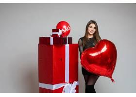 黑发女孩穿着黑色连衣裙手持红色心形气球_1192332801