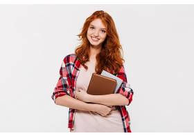 微笑的姜色女人穿着衬衫拥抱书籍的形象_733802201
