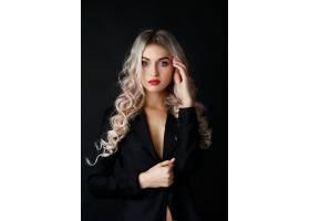 性感的金发长卷发在黑暗的工作室里穿着黑色_243763001