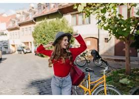 性感的长发女孩穿着红色毛衣在户外骑自行车_1097900201