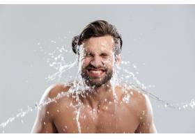 一名年轻男子孤零零地站在灰墙上洗脸_8078064
