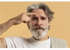 留着胡须指出皱纹的年长男子的正面图_9411363