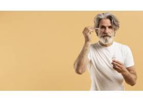 老年胡须男子涂抹血清的正面图_9411452