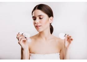 身穿白色上衣的年轻黑发女子正在看保湿面霜_12607420