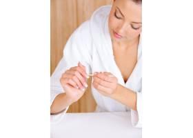 年轻漂亮的女性用化妆品棒去除手指的角质层_10362973