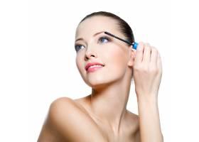 年轻漂亮的成年女子在孤立的白色睫毛上涂睫_10626568