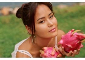 美丽的亚洲年轻女子手持火龙果的美人肖像_9275579