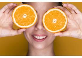 手持橘子片的可爱年轻女子_5445340