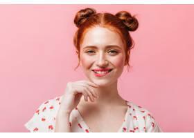 淘气的红头发女士粉色背景下眨着眼睛露_12678002