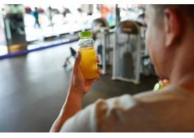 在肩上看到一个拿着一瓶橙汁的面目全非的人_5839398