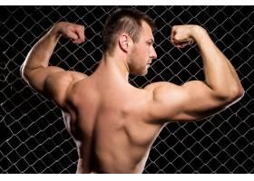 有权势的人在栅栏上展示他的肌肉_5904098