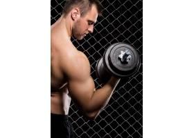 有权势的人拿着哑铃在栅栏上展示肌肉_5904100