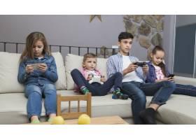 男孩玩电子游戏女孩使用智能手机_2062755