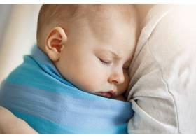 天真无邪的小孩子穿着蓝色婴儿吊带睡在母亲_8811702