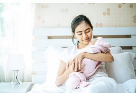 新生婴儿睡在母亲的怀抱里_5897172