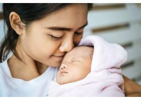新生的婴儿睡在母亲的怀里婴儿的额头上散_5897173