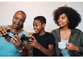 孩子教奶奶和妈妈玩电子游戏_9809259