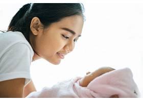 母亲看着躺在母亲手中的婴儿_5897169