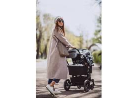 年轻的母亲坐在公园里的婴儿车里_4758581