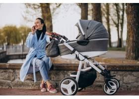 年轻的母亲坐在公园里的婴儿车里_4755324