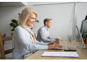 微笑的老年女商人在协同办公的办公室里使用_3954497