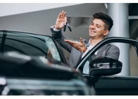 年轻英俊的商人在汽车展厅选车_6190347