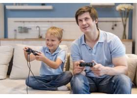 父亲和儿子一起玩电子游戏_10163912