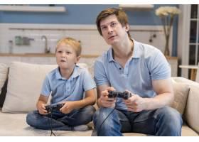 父亲和儿子一起玩电子游戏_10163920