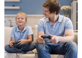 父亲和儿子一起玩电子游戏_10163925