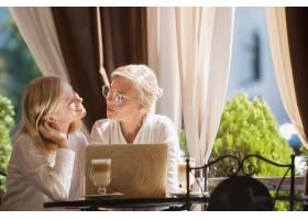 美丽成熟的母亲和她的女儿手持杯子坐在家里_7402526