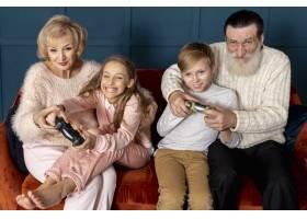前视祖父母和孙子孙女玩电子游戏_6748777