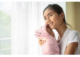 新生婴儿睡在母亲的怀抱里_5897162
