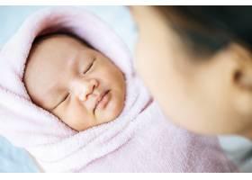 新生的婴儿睡在母亲的怀里_5897171