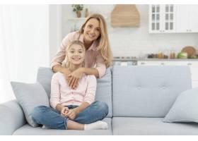 女儿坐在母亲怀抱的沙发上_5881550
